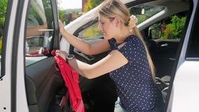 Vídeo de la cámara lenta de la mujer joven hermosa que limpia su coche del polvo con las sustancias químicas y el paño de la micr metrajes