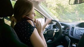 Vídeo de la cámara lenta de la mujer joven que habla por el teléfono mientras que conduce el coche almacen de video