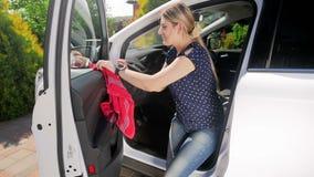 Vídeo de la cámara lenta de la mujer joven que limpia su coche con el paño Plástico de pulido del conductor en vehículo con micro