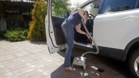 Vídeo de la cámara lenta de la mujer joven usando la aspiradora para limpiar su coche interior del polvo y de la suciedad Limpiez almacen de video