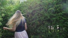 Vídeo de la cámara lenta de la mujer sonriente feliz que corre lejos de cámara en el parque y que mira sobre su hombro almacen de metraje de vídeo