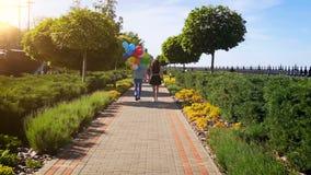 Vídeo de la cámara lenta de pares jovenes con el manojo de globos coloridos que caminan en el parque metrajes