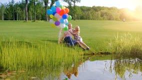 Vídeo de la cámara lenta de pares jovenes felices en el amor que sostiene los globos coloridos y que se relaja por el río almacen de video