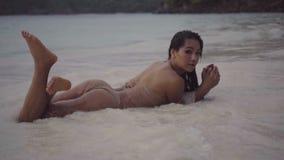 Vídeo de la muchacha atractiva que miente en la arena con salpicar el agua y la mudanza sensual en la cámara lenta metrajes