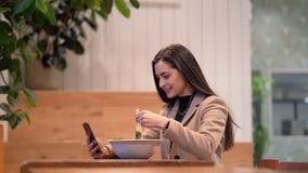 Vídeo de la muchacha que come una ensalada y que usa el teléfono celular almacen de video