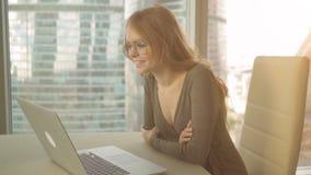 Vídeo de la mujer joven que llama a sus amigos que usan un ordenador portátil en el fondo de la ciudad almacen de video