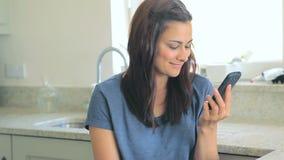 Vídeo de la mujer que se sienta en la cocina almacen de video