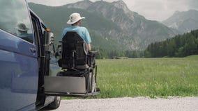 vídeo de la resolución 4k de un hombre en la salida de la silla de ruedas de un coche en el vehículo especializado elevación eléc metrajes