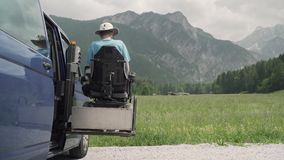 vídeo de la resolución 4k de un hombre en la salida de la silla de ruedas de un coche en el vehículo especializado elevación eléc almacen de video