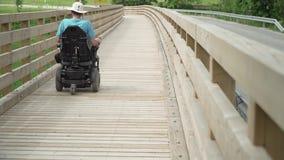 vídeo de la resolución 4k de un hombre en la silla de ruedas eléctrica que conduce en el puente de madera almacen de metraje de vídeo