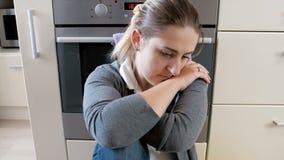 vídeo de la toma panorámica del primer 4k de la mujer joven cansada triste que se sienta y que llora en piso en la cocina metrajes