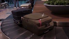 Vídeo de los equipajes que esperan del viajero de la gente para en una banda transportadora en el aeropuerto almacen de metraje de vídeo