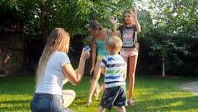 vídeo de los niños de risa alegres que cogen las burbujas de jabón que la madre está soplando en parque almacen de metraje de vídeo