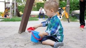 Vídeo de movimento lento de 2 anos adoráveis da areia de escavação do menino idoso da criança e o derramamento dele na cubeta no  video estoque