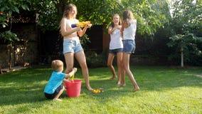 Vídeo de movimento lento de crianças felizes e dos adultos que espirram a água das armas de água e da mangueira de jardim sobre s video estoque