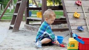 Vídeo de movimento lento da areia de escavação e do derramamento do menino bonito da criança na cubeta plástica no campo de jogos vídeos de arquivo