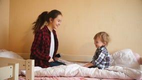 Vídeo de movimento lento da dança feliz do menino e do adolescente da criança e do salto na cama video estoque