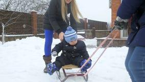 Vídeo de movimento lento da família que monta o menino feliz da criança em trenós no quintal video estoque