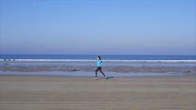 Vídeo de movimento lento da jovem mulher do ajuste que corre na praia filme