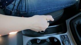 Vídeo de movimento lento do close up do motorista fêmea que puxa a alavanca de freio da mão no estacionamento vídeos de arquivo