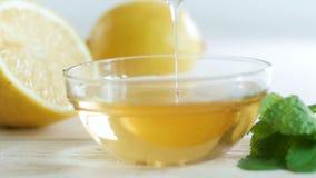 Vídeo de movimento lento do mel que goteja lentamente da colher após ter posto a no frasco do mel vídeos de arquivo