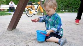 Vídeo de movimento lento do menino bonito da criança que joga com pá e cubeta do brinquedo na caixa de areia no campo de jogos vídeos de arquivo