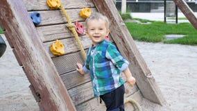 Vídeo de movimento lento do menino de sorriso alegre da criança que joga no campo de jogos com a parede de madeira para escalar filme