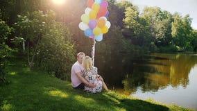 Vídeo de movimento lento de pares novos bonitos no amor que senta-se o lago e pelo beijo filme