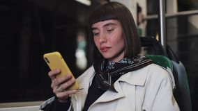 Vídeo de observação da jovem mulher atrativa no smartphone no transporte público Ponte do louro em San Francisco, CA Close-up Luz filme