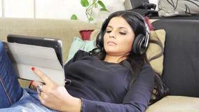 Vídeo de observação da jovem mulher bonita no PC da tabuleta vídeos de arquivo