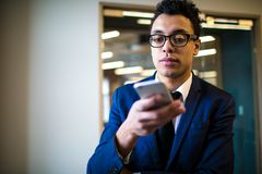 Vídeo de observação da liderança masculina pensativa no Internet através do smartphone Pagamento em linha imagens de stock royalty free