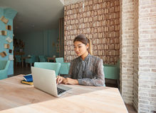 Vídeo de observación de la mujer alegre en el ordenador portátil mientras que espera su café de la orden foto de archivo