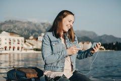 Vídeo de observación de la mujer feliz en el teléfono en el muelle cerca del mar Foto de archivo libre de regalías