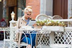 Vídeo de observación de la mujer hermosa en la tableta digital mientras que se sienta en café de la acera en día de primavera dur Fotografía de archivo libre de regalías