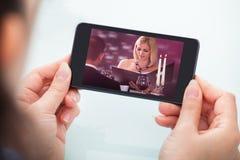 Vídeo de observación de la persona en el teléfono móvil Imagenes de archivo