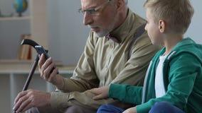 Vídeo de observación envejecido del hombre y del nieto en smartphone junto, proximidad de la familia almacen de metraje de vídeo