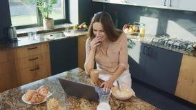 Vídeo de observación de la mujer feliz en cocina Persona femenina sonriente que mira el ordenador