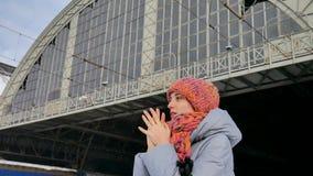 Vídeo del aire libre del viajero femenino que espera en el ferrocarril durante día de invierno soleado pero frío Concepto del via almacen de video