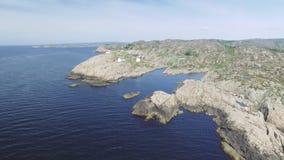 Vídeo del faro en verano, Noruega del sur de Lindesnes Tiro aéreo Costa de mar rocosa y cielo azul metrajes