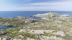 Vídeo del faro en verano, Noruega del sur de Lindesnes Tiro aéreo Costa de mar rocosa y cielo azul almacen de metraje de vídeo