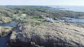 Vídeo del faro en verano, Noruega del sur de Lindesnes Tiro aéreo Costa de mar rocosa y cielo azul almacen de video