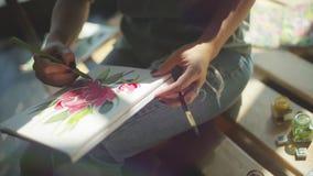 Vídeo del fondo: el artista hace manchas y dibuja una botánica de la flor almacen de video