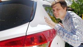 vídeo del hombre joven sonriente que toca a mano su nuevo coche limpio almacen de video