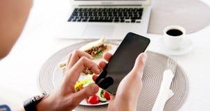 vídeo del hombre que usa smartphone con el almuerzo metrajes