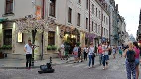 Vídeo del PDA de la gente que camina en una calle de la ciudad vieja Lviv y un hombre joven que toca el violín