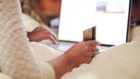 Vídeo del primer 4k de la mujer joven que usa el ordenador portátil y sosteniendo la tarjeta de crédito disponible Concepto de co almacen de metraje de vídeo
