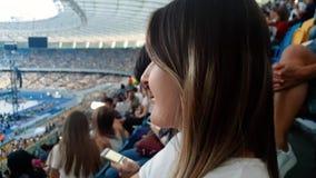 vídeo del primer 4k de la mujer joven sonriente hermosa con el pelo largo que se sienta en tribunas del estadio grande y de la ob almacen de video