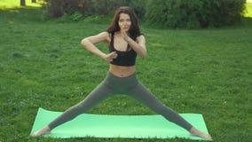 Vídeo divertido sobre la mujer joven que hace ejercicio de la yoga y que engaña alrededor al aire libre en parque en la mañana almacen de metraje de vídeo