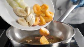 Vídeo do alimento do movimento lento do restaurante Cozinheiro chefe que põe o fruto cortado: banana, abricós na frigideira Cozin vídeos de arquivo