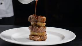 Vídeo do alimento no movimento lento Molho de derramamento do cozinheiro chefe no bife franzido Serviço do prato da carne do rest filme